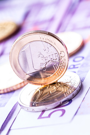 Several 500 euro banknotes and coins are adjacent. Symbolic photo for wealt.Euro coin balancing on stack with background of banknotes. photo