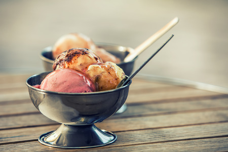 coppa di gelato: Gelato in due ciotole di metallo retrò su un tavolo di legno. Sfondi creati per il vostro testo. Archivio Fotografico