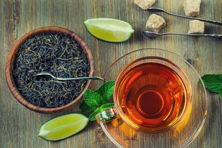 tazza di te: Tè in una tazza di vetro, foglie di menta, tè secche, fette di lime, zucchero di canna marrone