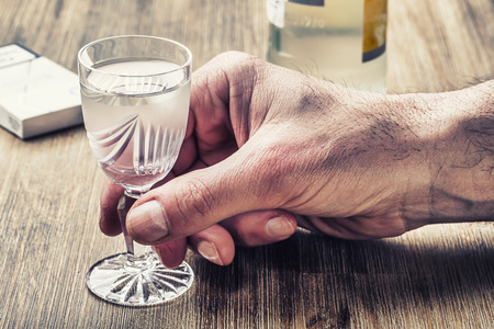 distillate: Alcoholism. Hand alcoholic and drink the distillate Stock Photo