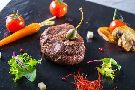 porterhouse: Grilled Beef steak with vegetable decoration. Grilled porterhouse steak on slate board. Stock Photo