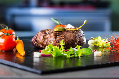 Grilled Beef steak with vegetable decoration. Grilled porterhouse steak on slate board. Stock Photo