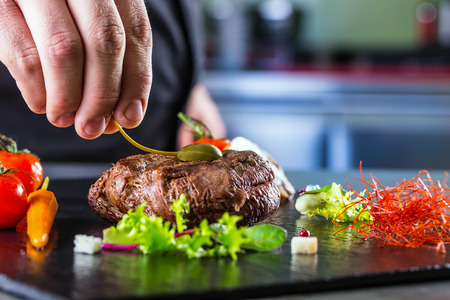 restaurant dining: Chef in hotel or restaurant kitchen cooking only hands. Prepared beef steak with vegetable decoration