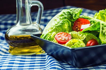 salad plate: Ensalada de lechuga fresca con tomates cherry r�bano y jarra con aceite de oliva en la mesa de madera. Varios ingredientes de la cocina mediterr�nea Foto de archivo
