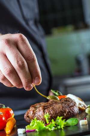 Chef in hotel or restaurant kitchen cooking only hands. Prepared beef steak with vegetable decoration photo