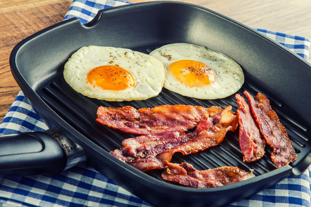 teflon: Ham and Egg. Bacon and Egg. Salted egg and sprinkled with black pepper. English breakfast. Grilled bacon two eggs in a Teflon panchecked on blue towel on wooden table