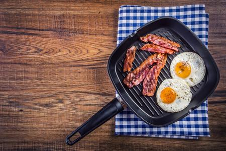 huevos fritos: Jam�n y huevo. Bacon y huevo. Salado huevo y espolvoreado con pimienta negro. Desayuno Ingl�s. Tocino a la plancha dos huevos en un tefl�n panchecked sobre una toalla azul en la mesa de madera Foto de archivo