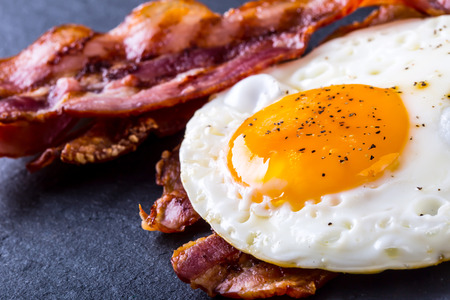 breakfast eggs: Ham and Egg. Bacon and Egg. Salted egg and sprinkled with black pepper. English breakfast. Stock Photo