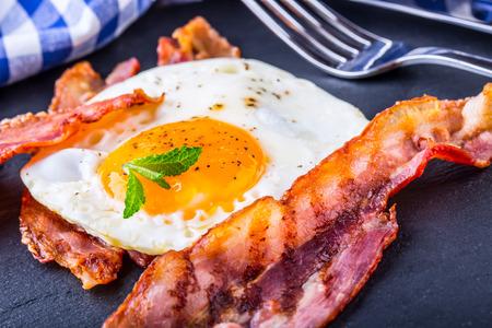 huevo: Jamón y huevo. Bacon y huevo. Salado huevo y espolvoreado con pimienta negro y decoración de la hierba verde. Desayuno Inglés. Foto de archivo