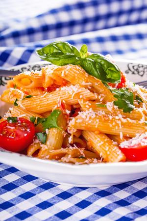 ajo: Placa con Bolognese pene pastas salsa de tomates cherry perejil parte superior y hojas de albahaca en mantel a cuadros azul. Cocina italiana y mediterr�nea