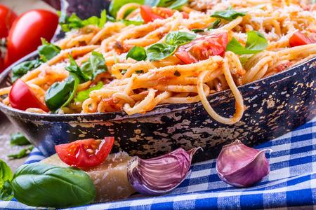 spaghetti sauce: Spaghetti. Italian and Mediterranean cuisine. Spaghetti bolognese with cherry tomato and basil. Spaghetti with tomato sauce on blue checkered tablecloth and rustic wooden table. Stock Photo