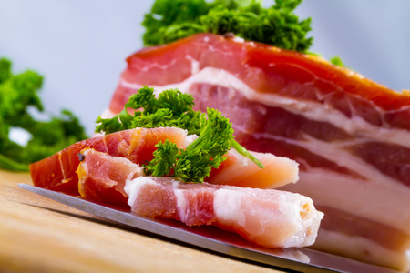 smoked bacon: Fresh smoked bacon with herbs on the white plate,closeup Stock Photo