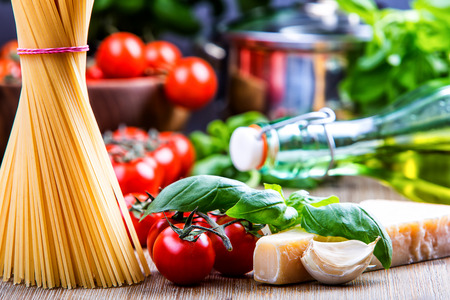 Italian and Mediterranean food ingredients on old wooden background.spaghetti olives basil cherry tomato pesto pasta garlic pepper olive oil and mortar. Stock Photo