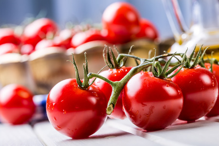 Tomaten. Cherry-tomaten. Cocktailtomaten. Verse druiven tomaten karaf met olijfolie op tafel.