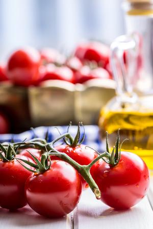 tomato cocktail: Tomatoes. Cherry tomatoes. Cocktail tomatoes. Fresh grape tomatoes carafe with olive oil on table. Stock Photo