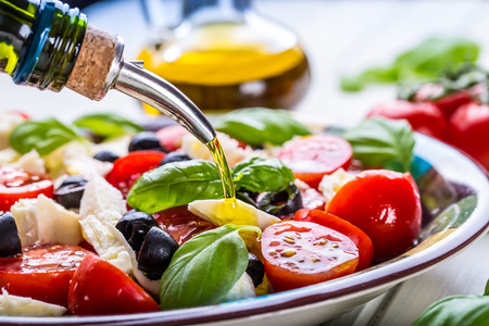 salads: Caprese. Caprese salad. Italian salad. Mediterranean salad. Italian cuisine. Mediterranean cuisine. Tomato mozzarella basil leaves black olives and olive oil on wooden table. Recipe - Ingredients