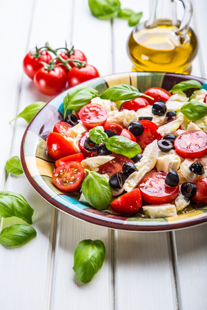 salad plate: Caprese. Caprese salad. Italian salad. Mediterranean salad. Italian cuisine. Mediterranean cuisine. Tomato mozzarella basil leaves black olives and olive oil on wooden table. Recipe - Ingredients