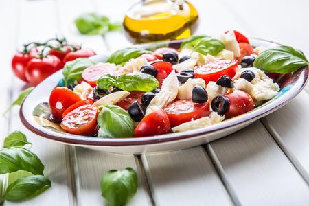salad: Caprese. Caprese salad. Italian salad. Mediterranean salad. Italian cuisine. Mediterranean cuisine. Tomato mozzarella basil leaves black olives and olive oil on wooden table. Recipe - Ingredients