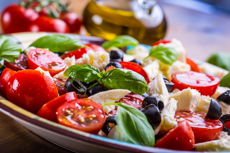 antipasto: Caprese. Caprese salad. Italian salad. Mediterranean salad. Italian cuisine. Mediterranean cuisine. Tomato mozzarella basil leaves black olives and olive oil on wooden table. Recipe - Ingredients