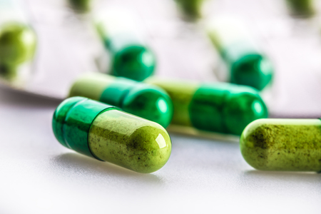 pills: Pills. Tablets. Capsule. Heap of pills. Medical background. Close-up of pile of yellow green tablets - capsule