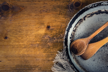 Wooden kitchen utensils on the table. Wooden spoon old pan in a retro style on wooden table. Free space for your information and products. Stock Photo