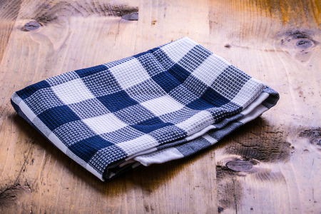 loosely: Canvas checkered cloth loosely laid on a wooden table