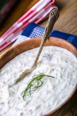 salad decoration: Tzatziki. Greek salad tzatziki  of cucumber, yogurt or cream, olive oil, garlic, dill and spices. Herb decoration of dill. Stock Photo