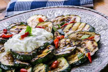 grill pattern: Zucchini. Grilled zucchini. Slices of grilled zucchini on a plate. Vegetarian - Mediterranean cuisine.
