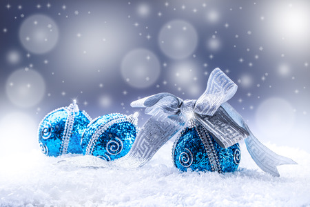 december: Christmas.Christmas blue balls and silver ribbon snow and space abstract background.