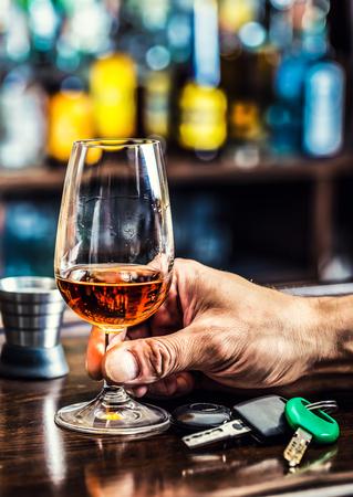 alcoholismo: Alcoholismo. Copa de co�ac o brandy de la mano del hombre las llaves del coche y un conductor irresponsable. Foto de archivo