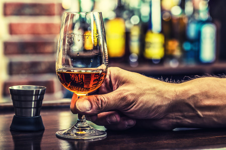 alcoholismo: Alcoholismo. Mano alcohólica y beber el aguardiente destilado o coñac.
