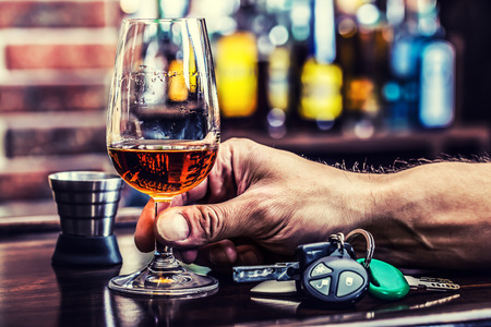 borracho: Alcoholismo. Copa de coñac o brandy de la mano del hombre las llaves del coche y un conductor irresponsable. Foto de archivo