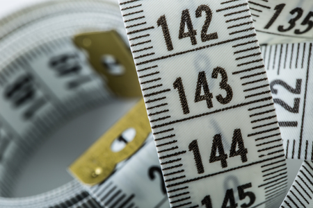 made to measure: Curved measuring tape. Measuring tape of the tailor. Closeup view of white measuring tape