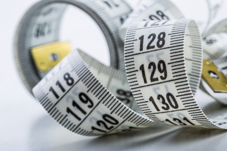 measure: Curved measuring tape. Measuring tape of the tailor. Closeup view of white measuring tape