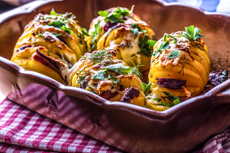 potato: Potato.Roasts potatoes. Home cooking roasts potatoes. Baking pan full of baked potatoes stuffed with bacon sausage onions and grated cheese flavored with caraway seeds salt pepper and fresh herbs parsley and dill
