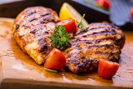 Grilled chicken in different variations with cherry tomatoes, green French beans, garlic, herbs, cut lemon on a wooden board or teflon pan. Traditional cuisine. Grill kitchen.