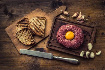 steak tartare:  Classic steak tartare on wooden board.  Stock Photo
