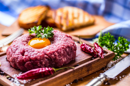 Classic steak tartare on wooden board. Ingredients: Raw beef meat salt pepper egg garlic chilli herb decoration and toast bread Stock Photo