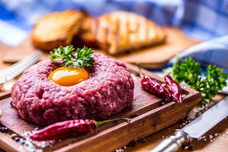 Klassieke steak tartare op een houten bord. Ingrediënten: Ruw rundvleesvlees zout peper ei knoflook chili kruid decoratie en toast brood Stockfoto