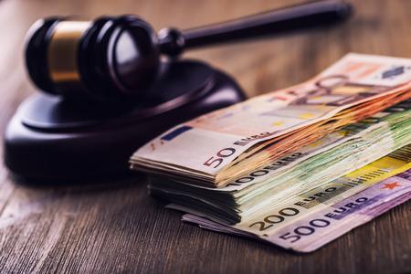 裁判官のハンマーの小槌。正義とユーロのお金。ユーロ通貨。裁判所小槌や圧延ユーロ紙幣。司法の不正収賄容疑の表現。 写真素材
