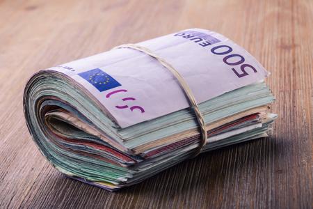 dinero euros: Los billetes en euros. Moneda euro. Euro dinero. Primer plano de una cifra de billetes en euros enrollado en mesa de madera Foto de archivo