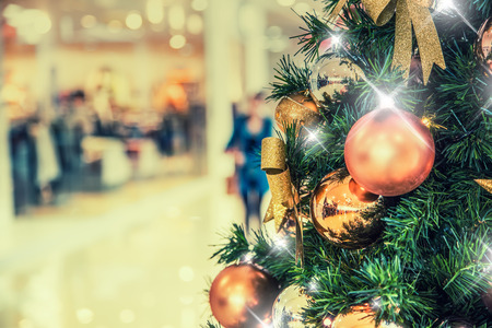 holiday display: Christmas tree with gold decoration in shopping mall.Christmas clearance sales at the shopping mall. Elegant Christmas tree in a shopping mall