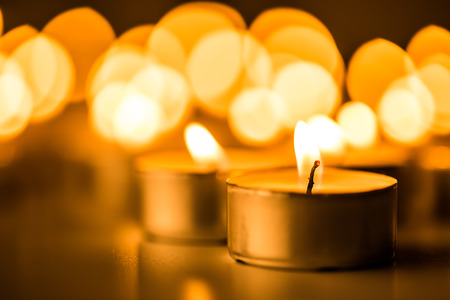 flame background: Candles light. Christmas candles burning at night. Abstract candles background. Golden light of candle flame.