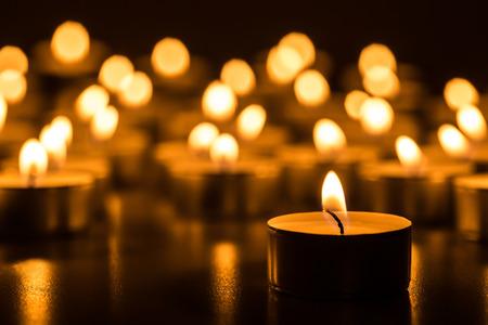 the church: Velas de luz. Velas de Navidad encendidas en la noche. Velas Resumen de antecedentes. Luz de oro de la llama de la vela.