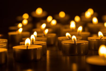 Kaarsen branden. Kerst kaarsen branden in de nacht. Abstracte kaarsen achtergrond. Gouden licht van de kaarsvlam.