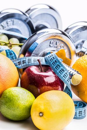 huincha de medir: mancuernas de cromo rodeados de frutas sanas cinta m�trica sobre un fondo blanco con sombras. dieta de estilo de vida saludable y el ejercicio. Foto de archivo