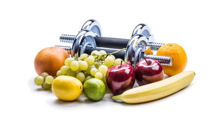 fresh concept: Chrome dumbbells surrounded with healthy fruits measuring tape on a  white background with shadows. Healthy lifestyle diet and exercise.