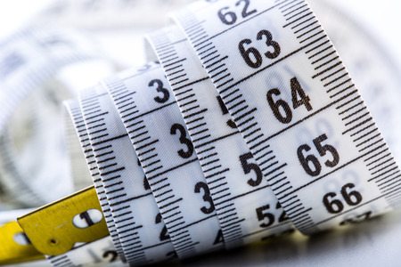 measurement: Curved measuring tape. Measuring tape of the tailor. Closeup view of white measuring tape