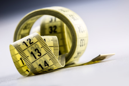 Curved measuring tape. Measuring tape of the tailor. Closeup view of white measuring tape