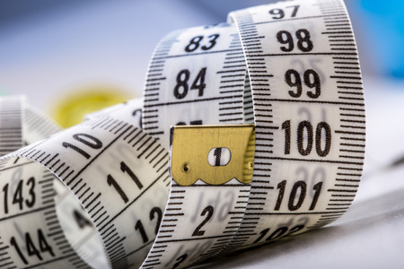 measure tape: Curved measuring tape. Measuring tape of the tailor. Closeup view of white measuring tape
